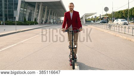 Handsome Caucasian Young Stylish Man In Red Jacket Standing On Electric Scooter At Urban Street Near