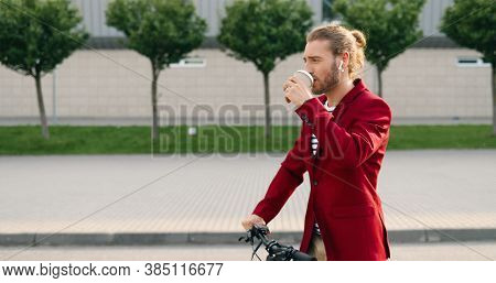 Handsome Caucasian Young Stylish Man In Headphones And Red Jacket Riding On Electric Scooter At Urba