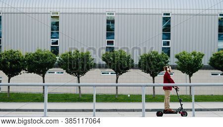 Caucasian Stylish Young Man In Headphones Riding Electric Scooter And Standing Still On Street In To