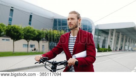Portrait Of Caucasian Handsome Young Man In Red Jacket Standing Outdoor With Bike Or Electric Scoote