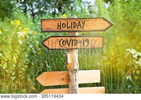 Wooden Direction Sign With  Words Holiday And Covid-19