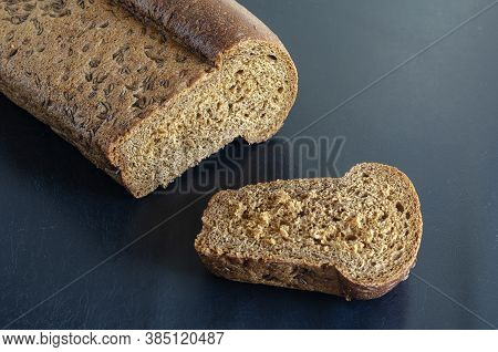 A Slice Of Rye Bread With Caraway Seeds Cut From A Loaf On A Black Background. Side View Of Freshly