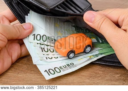 Woman Hands Hold An Open Black Leather Wallet With 100 Euro Banknotes And An Orange Toy Car. Concept