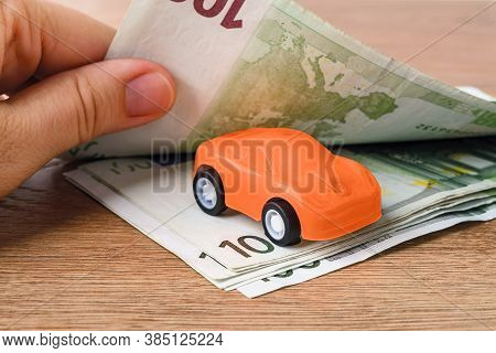 Orange Toy Car Between 100 Euro Banknotes. Woman Hands Count Paper Money. Concept Of Car Buying, Ren
