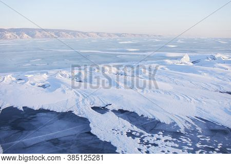 Snow On Lake Baikal Ice Near Olkhon Island. Winter Landscape