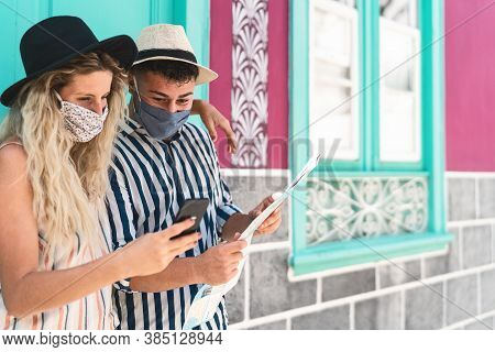 Young Couple Wearing Face Protective Mask While Using Mobile Phone And Holding Travel Map - Traveler