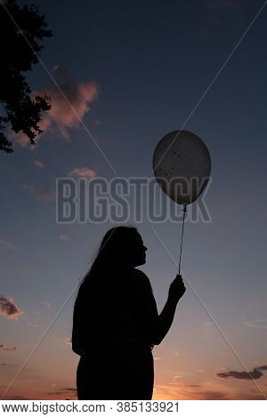Silhouette Of Female Holding Balloon With Hearts Against Sundown Purple Sky.