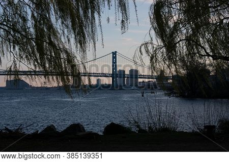 Looking Through Bright Green Trees At The Ben Franklin Bridge From The Newly Renovated Penn Treaty P