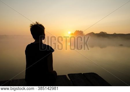 Silhouette Of A Girl Sitting On The Pier Against The Sunset Sky With Copy Space. The Girl Looking At