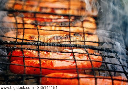 Bbq With Fiery Sausages Hotdog On The Grill Outdoor Picnic. Spending Time Together With The Family A