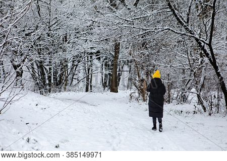 Woman In Black Winter Coat And Yellow Hat Walking By Snowed City Park