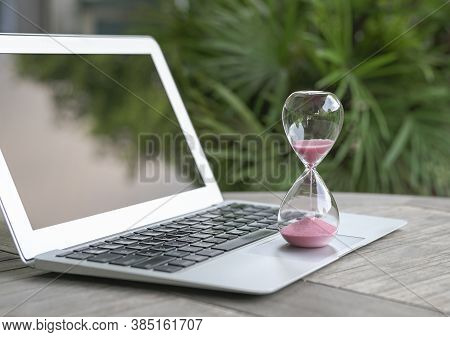 Hourglass On Laptop Computer. Time Management, Countdown And Deadlines Concept.
