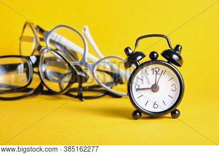 Alarm Clock And Several Different Eye Glasses On Yellow Background, Glasses For Children And Adults,