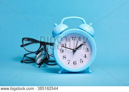 Alarm Clock And Several Different Eye Glasses On A Blue Background, Glasses For Children And Adults,
