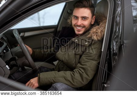 Young Adult Attractive Caucasian Man Sits At The Wheel Of His Car Sunny Winter Day. Wintertime Road