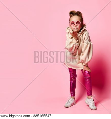 Serious Little Girl In Stylish Pink Attire And Round Glasses Leaning Forward Blowing A Kiss To Spect