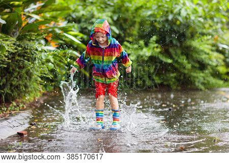 Kid Playing In The Rain In Autumn Park. Child Jumping In Muddy Puddle On Rainy Fall Day.