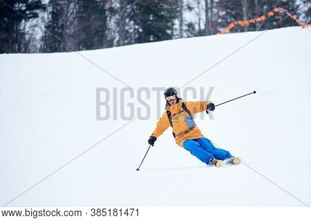 Professional Skier Concentrated On Skiing Down On Steep Ski Slope. Proficient Technical Carving Skii