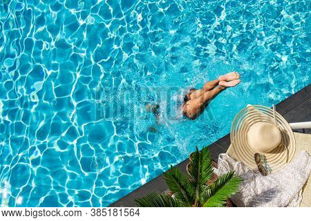 woman diving  at luxury five stars  spa resort in the swimming pool in Greece