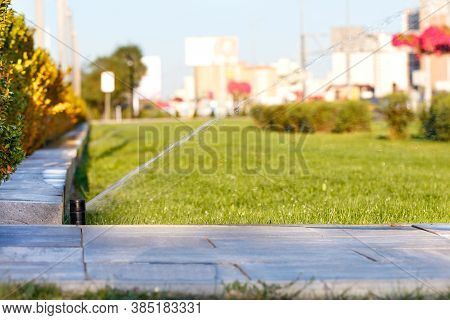 Automatic Irrigation System Irrigated The Lawn On A Blurred Background Of The Cityscape On A Bright