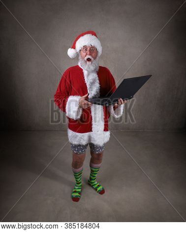 Santa holding a laptop attending an online remote internet meeting with his pants off
