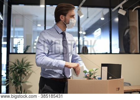 Dismissal Employee In Preventive Medical Mask In An Epidemic Coronavirus. Sad Dismissed Worker Are T