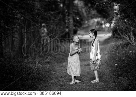 Two little girls in the pine forest. Black and white photo.