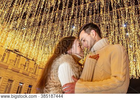 Night Portrait Of A Couple In Love On The Background Of Lights Of Garlands On A City Street