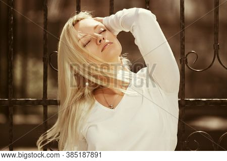 Young fashion blonde woman at the cast iron fence Stylish female model in white long sleeve shirt