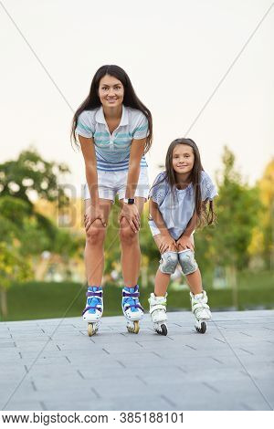 Young Pretty Mother With Her Little Daughter Rollerskating In Park. Smiling Mom And Child Girl Rolle