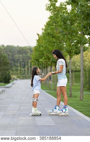 Young Mother And Her Pretty Little Daughter Rollerskating In Summer Park. Happy Family Have Fun