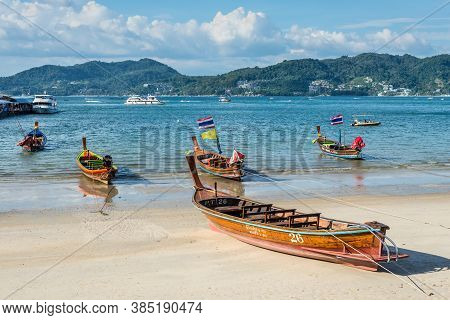 Phuket, Thailand - November 29, 2019: Traditional Longtail Boats With National Flag On The Shore Of