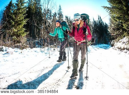 Two Women In A Winter Hike. Girlfriends With Trekking Poles Are On A Snow Covered Mountain Path. Gir