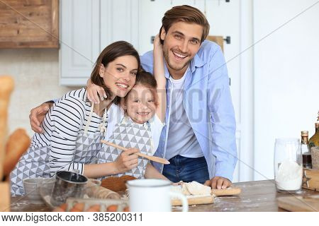 Cute Little Girl And Her Parents Are Having Fun While Cooking In Kitchen At Home Together.