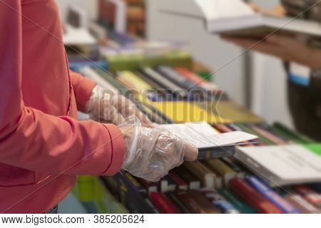 Abstract Person In Disposable Protective Gloves With Book In Hands, Library, Bookstore. New Normal.