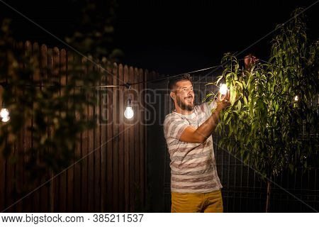 Party Time In Backyard With Happy Man Hanging String Lights In Trees - Weekend Night Mood With Smili