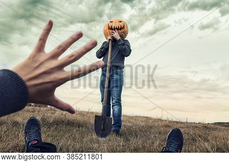Modern Jack-lantern With  Pumpkin On His Head And Shovel Looks At His Victim. Scene Through The Eyes