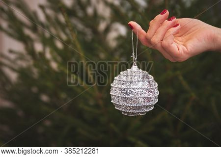 Closeup Of A Girls Hand With A Silver Ball Strewn With Confetti Decorate A Christmas Tree. Holiday S