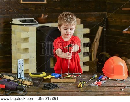 Cute Kid At Crafts Class. Boy Binding Screw To Wooden Board. Little Repairman Holding Screwdriver Wi