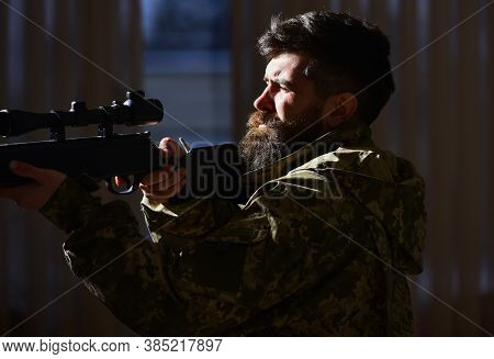 Man With Beard Wears Camouflage Clothing, Dark Interior Background. Hunter, Soldier With Gun Aiming