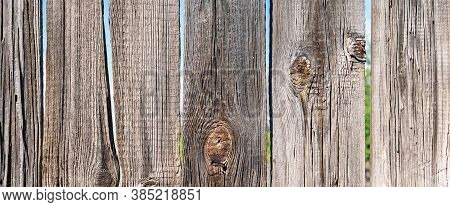 The Surface Of An Old Wooden Fence, Close-up. Brown Banner Background. Faded From The Sun, Dry Uncoa