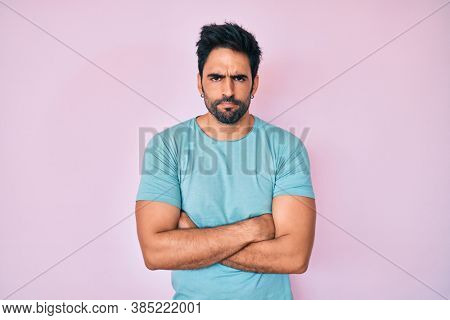 Handsome hispanic man with beard wearing casual clothes skeptic and nervous, disapproving expression on face with crossed arms. negative person.