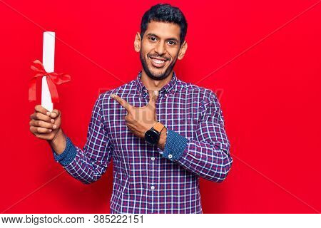 Young latin man holding graduate degree diploma smiling happy pointing with hand and finger