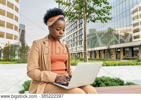 Young elegant businesswoman of African ethnicity with laptop on her knees sitting on wooden bench in park against office buildings