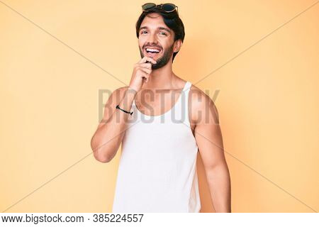 Handsome hispanic man wearing summer look and sunglasses looking confident at the camera with smile with crossed arms and hand raised on chin. thinking positive.