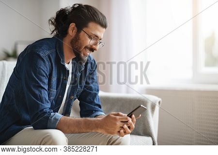 New Mobile App. Stylish Western Millennial Guy Using Smatphone While Sitting On Sofa At Home, Browsi