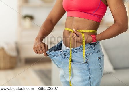 Slimming. African Woman After Weight Loss Measuring Thin Waist Wearing Oversize Jeans Standing Indoo