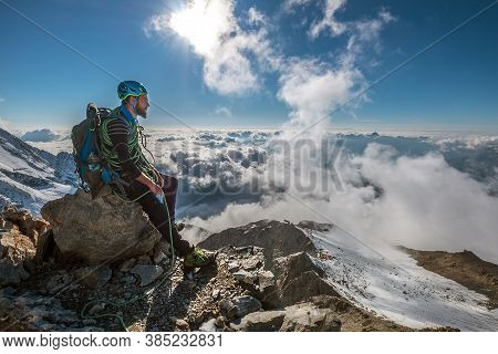 Bearded Climber In A Safety Harness, Helmet, And On Body Wrapped Climbing Rope With Sitting At 3600m