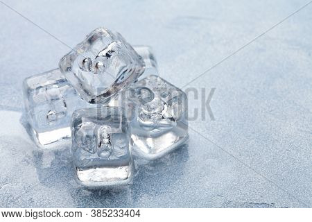 Ice cubes and water drops on stone background. With copy space