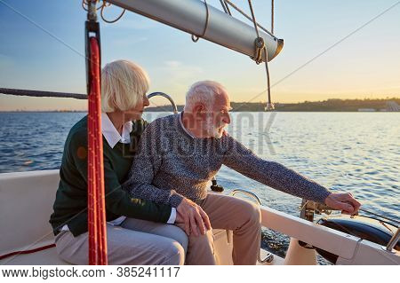People Lifestyle Concept. Senior Couple, Elderly Man And Woman Sitting On The Sailboat Or Yacht Deck